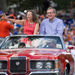 president kent fuchs and his wife in convertible in homecoming parade